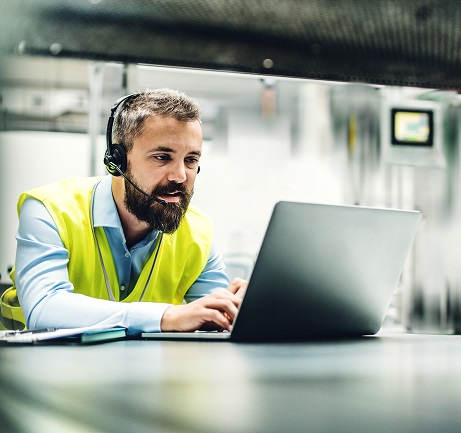 A portrait of a mature industrial man engineer with headset and laptop in a factory, working.